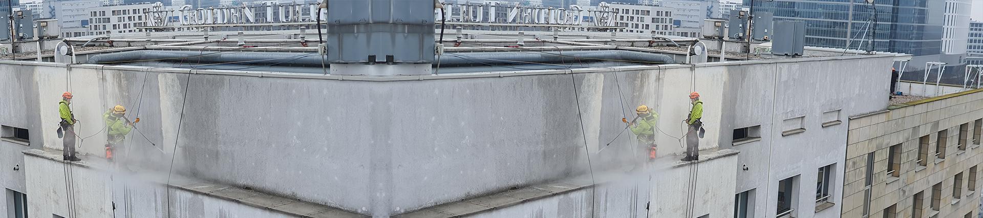 pracownicy czyszczą fasadę budynku